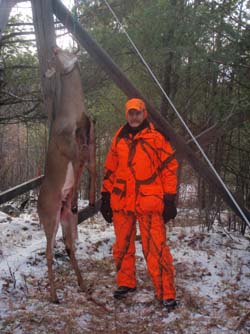 hunter in orange with deer hanging from tree