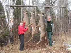 two hunters with three deer hanging