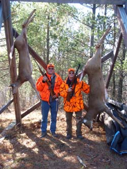 two hunters with two deer hanging