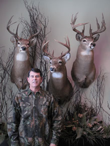 Dave Smith standing in front of 3 deer heads on a wall